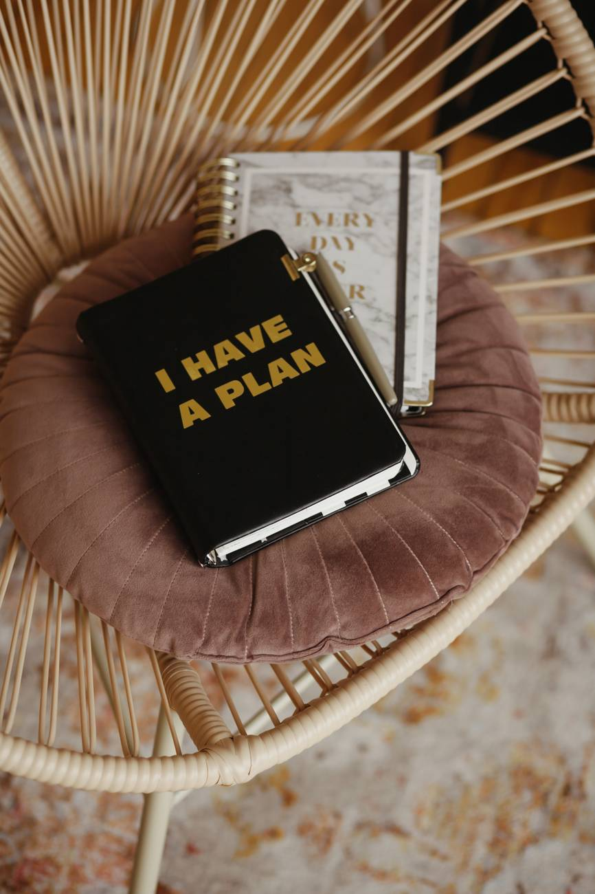 """Book with """"I have a Plan"""" written on the front.  Planner, organizer, sitting on a chair."""
